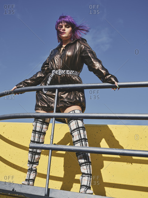 Fashion confident woman with purple hairstyle in shiny black jacket looking at camera in the city viewpoint with metal fence and yellow wall in bright day