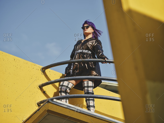 Fashion confident woman with purple hairstyle in shiny black jacket and sunglasses looking away on city viewpoint with metal fence and yellow wall in bright day