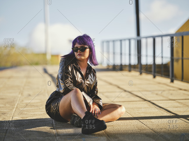 Content fashion woman in sunglasses with purple hairstyle in shiny black jacket looking away comfortably sitting on asphalt with crossed legs in sunny bright day