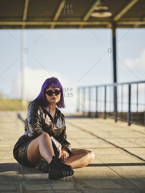 Content fashion woman in sunglasses with purple hairstyle in shiny black jacket looking at camera comfortably sitting on asphalt with crossed legs in sunny bright day