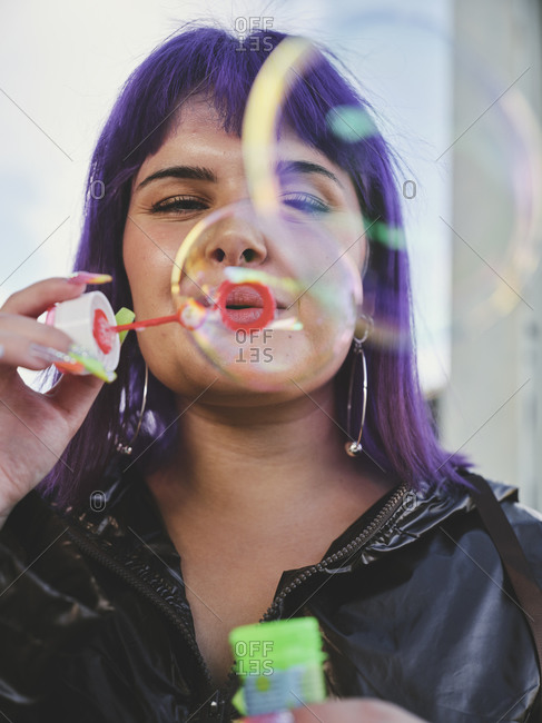 Fashion woman with purple hair smiling and blowing bubbles holding bottle while looking at camera with manicured hands in bright day