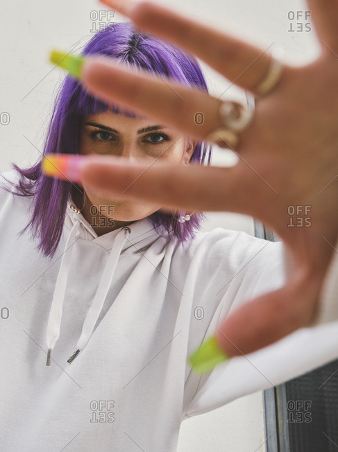 Fashion smiling woman with purple hair closing camera with manicured hand with rings on finger and looking at camera in bright day