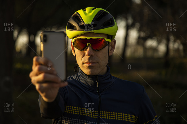 Man cyclist resting while using mobile phone to take a picture on the bike lane in a park