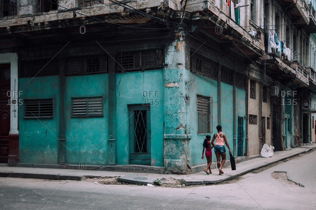 Havana, Cuba DECEMBER 14, 2019: Back view of local ethnic woman with girl walking on sidewalk next to old shabby residential building on city street