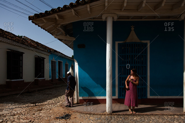 February 7, 2020: Havana, Cuba DECEMBER 14, 2019: People walking on the street of typical city with old colonial building and dilapidated house in Cuba