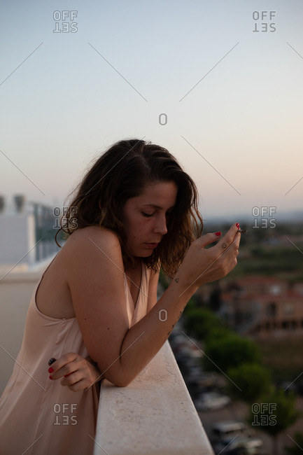 Side view of frustrated female in dress with crossed arms leaning on fence standing at balcony looking down