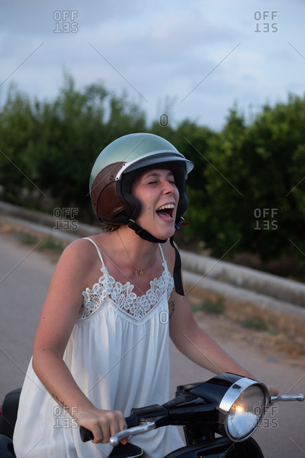 Cheerful woman on vacation in light clothing smiling with closed eyes on motorcycle in motion on the road