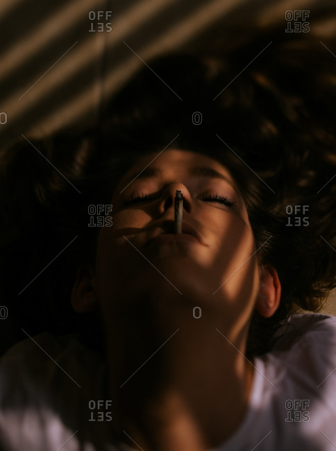 Woman lying down with closed eyes smoking cigarette