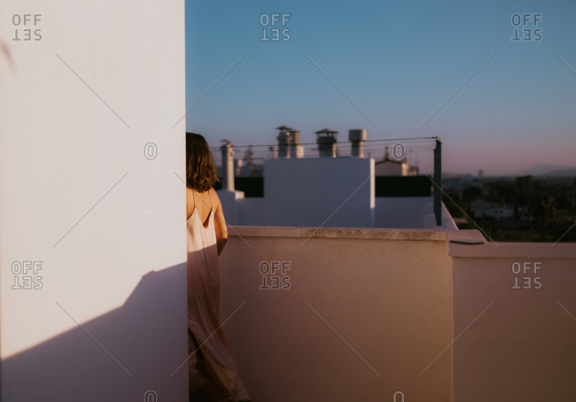 Back view of faceless female in light pink silk dress walking way around corner on rocked balcony with blue sky and green plants on background