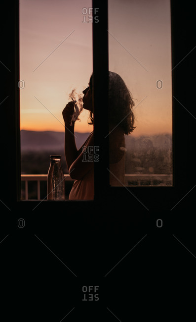 Side view of young faceless woman silhouette lighting cigarette with magnificent sunset on blurred background
