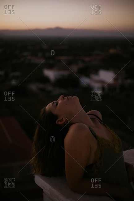 Peaceful woman leaning with closed eyes on fence of balcony with sunset on blurred background