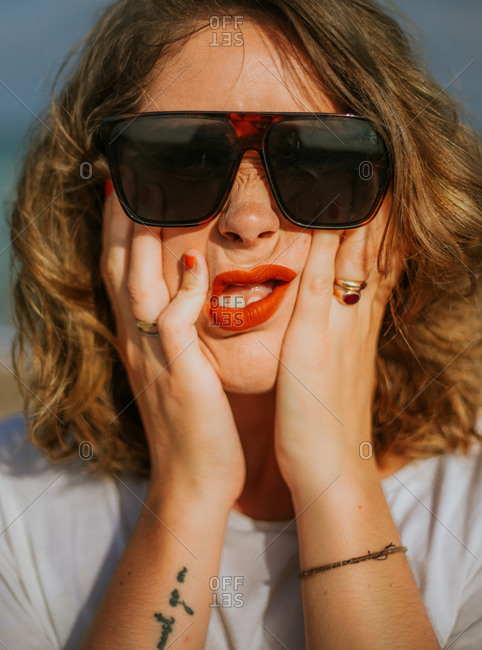 Stylish brown curly haired woman with red lipstick in trendy sunglasses looking at camera while squeezing face in palms
