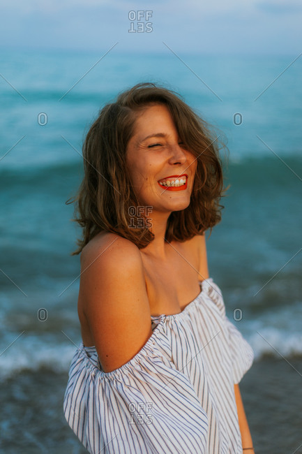 Happy woman in light dress walking among small sea waves on empty coastline at dusk with closed eyes