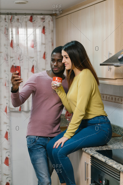 Charming long haired multiracial girlfriend sitting on table with cup while pleased African American man taking selfie on smartphone