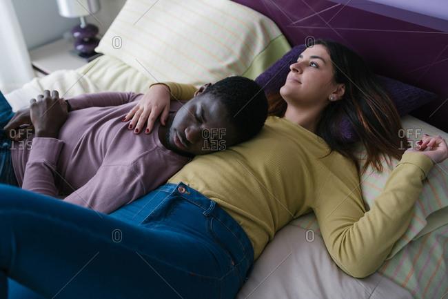 Stylish African American man sleeping on breast of thoughtful long haired woman bonding and looking away lying in soft bed in light bedroom