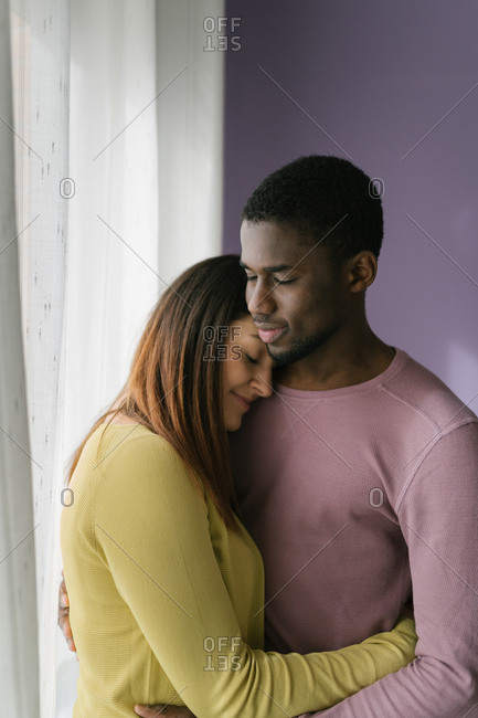 Pleased multiracial woman with closed eyes hugging black man in kitchen