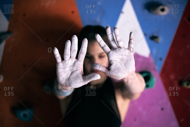 Anonymous climber preparing for climbing and showing at camera palms covered with sports talcum powder covering face on background of colorful wall for mountaineering