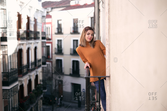 Bright young lady in casual clothes standing at balcony looking at camera