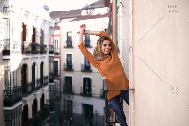 Bright young lady in casual clothes with raised hands standing at balcony looking at camera