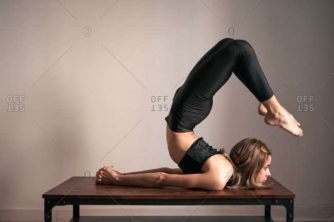 Side view of serious active young woman doing yoga in Scorpion Pose on table practicing meditation at home