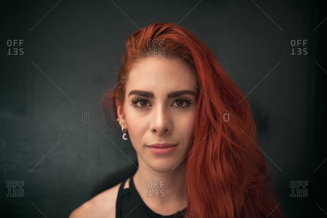 Calm gorgeous young lady with red hair standing at home looking at camera