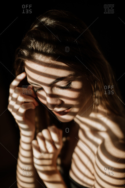Stripe shadow from shutters falling on face of charming relaxed long haired woman smiling with closed eyes
