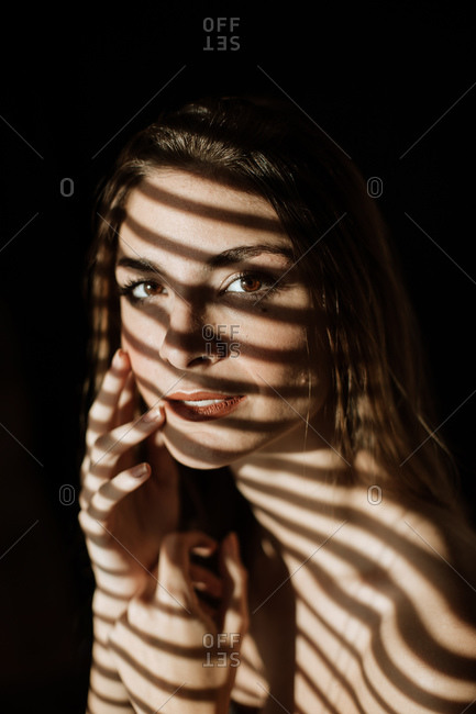 Stripe shadow from shutters falling on face of charming relaxed long haired woman smiling looking at camera