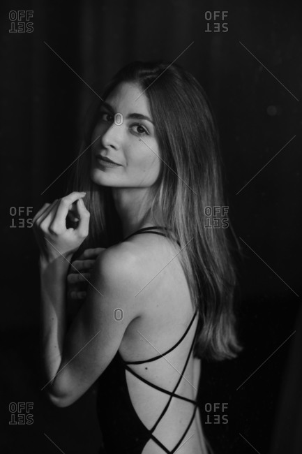 Long haired stylish woman in dark dress with with open back lacing alluringly looking over shoulder at camera on black background