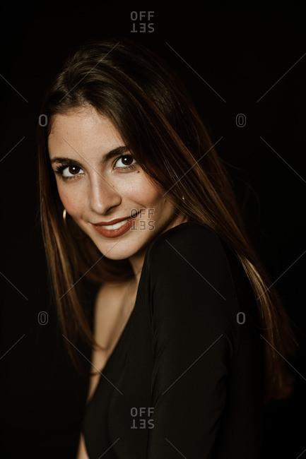 Sensual gorgeous woman in dark dress looking at camera