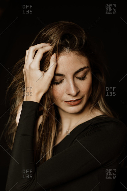 Sensual gorgeous woman in dark dress touching long shiny hair and thinking with closed eyes