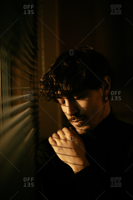 Young melancholic guy in black turtleneck standing next to window with shutters with shadow on face