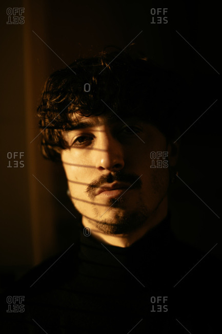 Young melancholic guy in black turtleneck standing next to window with shutters with shadow on face looking at camera