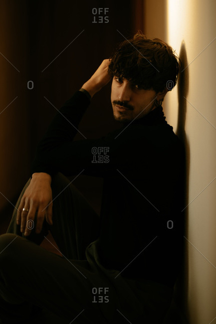 Young man with mustache sitting next to wall and running fingers through hair looking at camera