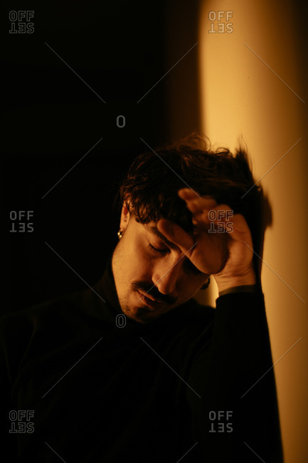 Young man with mustache sitting next to wall and running fingers through hair while tilting head down with closed eyes