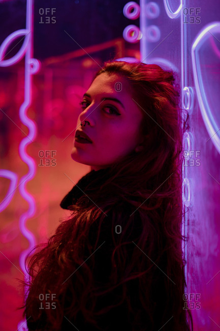 Stylish long haired brunette in casual wear looking at camera among neon signs at city street