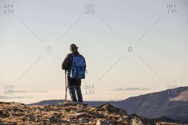 Back view of anonymous person with backpack and sticks travelling in mountain dry valley under blue sky in bright sunshine