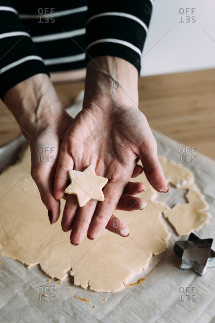 From above unrecognizable female chef showing homemade star shape cookie during baking festive biscuits in kitchen