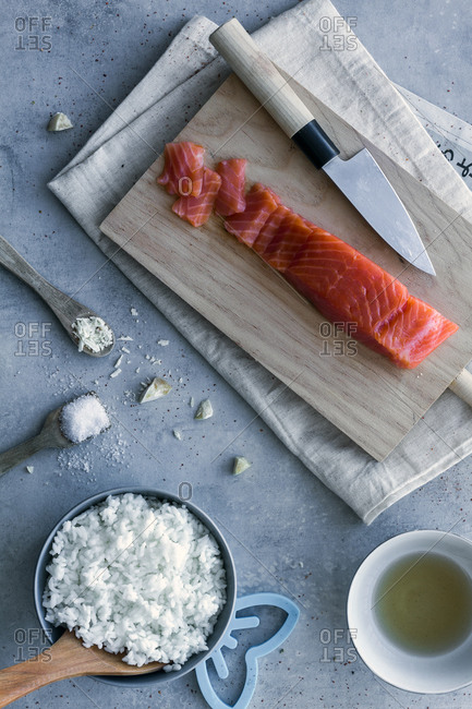 From above appetizing fresh sliced salmon and white tasty rice on table with wooden spoon and knife