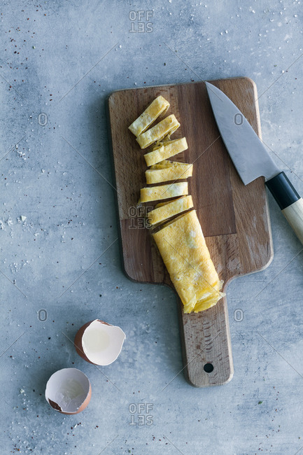 From above tasty fresh cut egg omelet with egg shells and knife on table