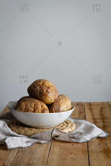 Stuffed brown potatoes in white bowl on towel on wooden table with white wall on background