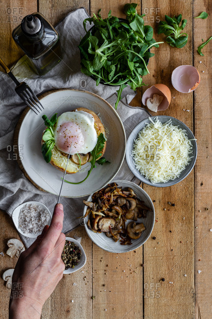 Top view of crop hand with knife cutting fried egg on potato on wooden table with fried mushrooms grated cheese and herbs