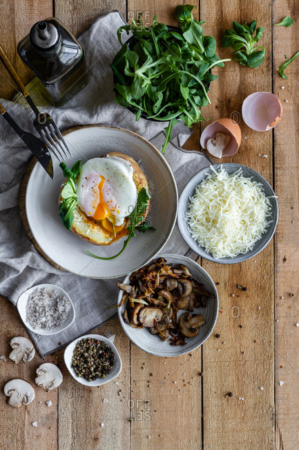 Top view fried egg on potato on wooden table with fried mushrooms grated cheese and herbs