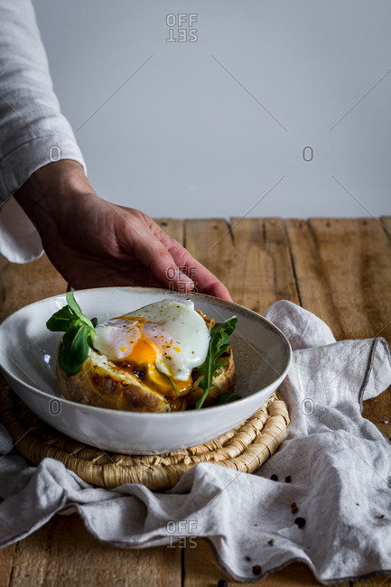 Crop anonymous hand holding dish with fried egg on potato on wooden table with fried mushrooms grated cheese and herbs