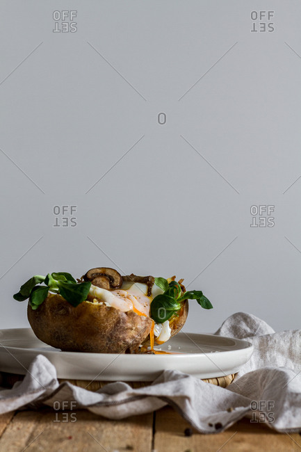 Fried egg on potato on wooden table with fried mushrooms grated cheese and herbs