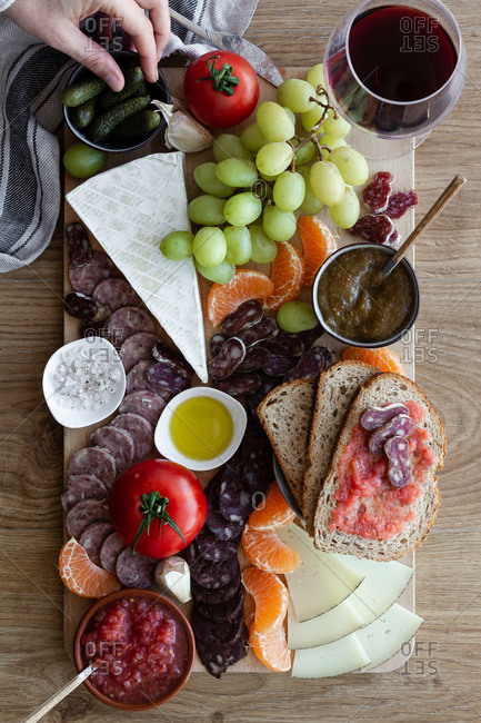 From above faceless cropped person hands eating snacks from wooden tray with sliced of meat vegetables fruits and glass of red wine