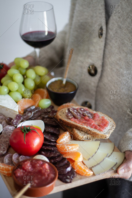 Faceless waiter carrying wooden tray with sliced of meat vegetables fruits and glass of red wine