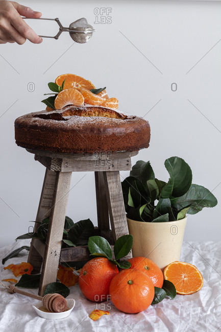 Crop anonymous person pouring sugar powder with metal round tea strainer above fresh appetizing cake on wooden stool surrounded by orange ripe tangerine and green plant in pot