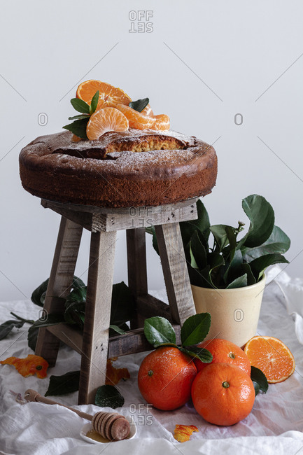 Picturesque still life of fresh appetizing cut and whole tangerine fresh tasty cake on small wooden stool and green plant in pot