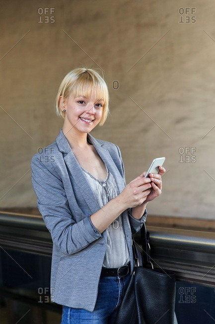 Cheerful blonde businesswoman holding smartphone and looking at camera at handrail