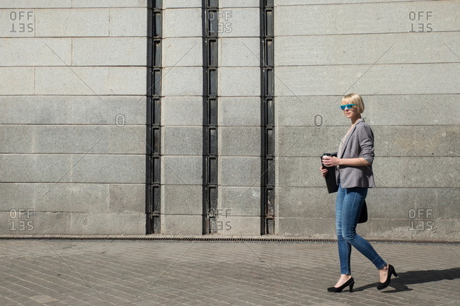Side view of pretty blonde businesswoman in formal jacket walking with folder and paper cup at concrete wall on sunny street